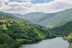 Wide calm river running through green forested hills in southern Bulgaria. On sunny summer day Royalty Free Stock Photography