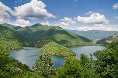 Wide calm river running through green forested hills in southern Bulgaria. On sunny summer day Royalty Free Stock Photo