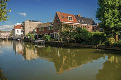 Wide canal with brick houses and boat moored on its bank reflected in water under blue sky of sunset in Weesp. Quiet and pleasant village full of canals and Royalty Free Stock Photography