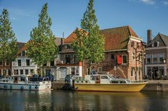Wide canal with brick houses, boats moored on its bank reflected in water and blue sky of sunset in Weesp. Stock Photo