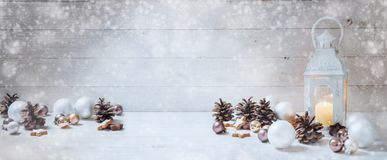 Wide christmas background with a candle light lantern, baubles,. Cinnamon stars, cones and snoe on rustic bright wood, panorama format for website banner, copy Stock Image