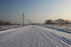 Wide cleared desert winter road between the villages among the fields covered with snow with high-voltage towers on the roadside. Wide cleared desert winter road stock image