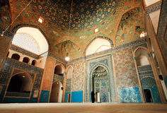Wide colorful hall of ancient mosque and lonely woman praying inside Royalty Free Stock Photo