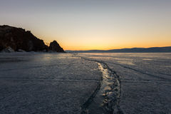 Wide crack in the ice of Lake Baikal to the Shaman Rock Stock Photos