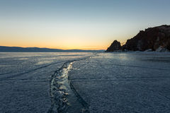 Wide crack in the ice of Lake Baikal to the Shaman Rock Royalty Free Stock Photos