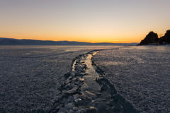 Wide crack in the ice of Lake Baikal to the Shaman Rock Royalty Free Stock Images