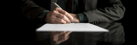 Wide cropped view of a businessman in business suit signing cont stock photos