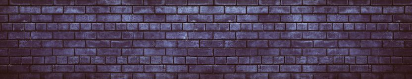 Wide dark violet brick wall gloomy grunge background stock photo