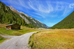 Wide dirt road in an Alpine valley Stock Photos