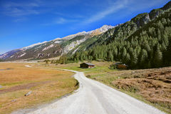 Wide dirt road in an Alpine valley Royalty Free Stock Image