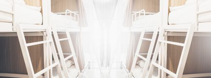 Wide dormitory beds inside the hostel room for tourists or the students blurred background banner. Wide dormitory beds inside the hostel room for tourists or the royalty free stock photos