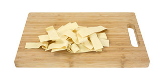 Wide egg noodles on wood cutting board Royalty Free Stock Image