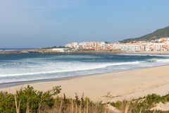 Wide empty beach with beautiful waves and white town on background. Vila Praia de Ancora, Portugal, landmark. Panoramic Atlantic Ocean coast with calm beach royalty free stock photography
