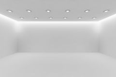 Wide empty white room with small round ceiling lamps. Abstract architecture white room interior - wide empty white room with white wall, white floor, white Royalty Free Stock Photos
