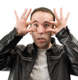Wide Eyed. A young man wearing a leather jacket is holding his eyes open, isolated against a white background Stock Photos