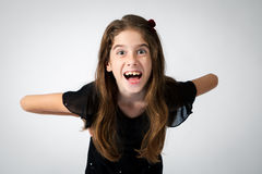 Wide Eyed Excited Girl. Portrait of a wide eyed, expressive girl on a white background.  She is leaning forward with an open mouth Royalty Free Stock Photo