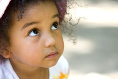 Wide Eyed Innocence. A cute little mixed race girl with a look of wide eyed innocence Stock Photos