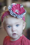 Wide-eyed toddler girl. Blond toddler girl with wide bright blue eyes; wearing a dark pink and zebra striped floral headband Stock Photos