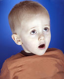 A wide eyed toddler looks surprised Stock Images