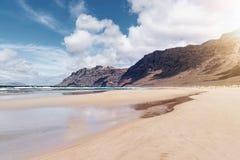 Wide Famara Beach on Lanzarote, Spain against Atlantic ocean, steep mountains and beautiful sky. Wide sandy Famara Beach on Lanzarote, Spain against Atlantic royalty free stock photos