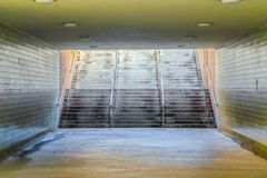 Wide flight of stairs at a passageway under a building with brick wall royalty free stock images