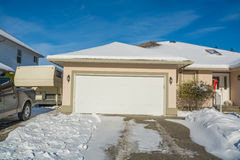 Wide garage of big luxury house with parked car and RV trailer beside. Driveway and entrance of residential house on winter sunny day Royalty Free Stock Image