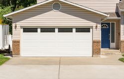Wide garage door of residential house and concrete driveway in front. Wide garage door of residential house and concrete driveway in front royalty free stock images