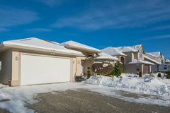 Wide garage of luxury house with driveway and front yard in snow. Street of residential houses on winter sunny day Stock Photos