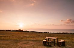 Wide Grass field by the ocean in Ishigaki island, Okinawa, Japan. Wide Grass field by the ocean with picnic table at sunset or sunrise in Ishigaki island Stock Photo