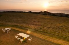 Wide Grass field by the ocean in Ishigaki island, Okinawa, Japan. Wide Grass field by the ocean with picnic table at sunset or sunrise in Ishigaki island Stock Image