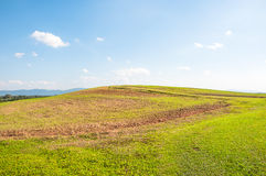 wide green field on rolling hills and blue sky with clouds among Royalty Free Stock Photos