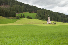 A wide green mountain pasture in Val di Funes, Italy Stock Image