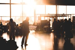 Male watching at crowd in airport. Wide hall of airdrome under sunset. Full length man looking at different people situating there Royalty Free Stock Image