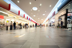 Wide hall and buyers in trading centre with shops Stock Image