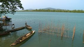 Landscape of a fishing river, Raphine, Myanmar. Wide high-angle panoramic panning shot of stationary local fishing canoes and traditional fish-traps, a huge stock video footage