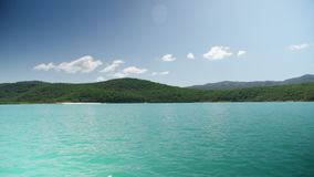 Sunny day in the middle of the sea. A wide idyllic shot of a blue sea water and a mountain surrounded by green trees and plants stock footage