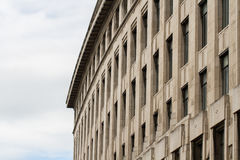Wide Imposing Building. The facade of large, imposing building with a curved front and rows of Windows in a city environment with copy space Stock Image
