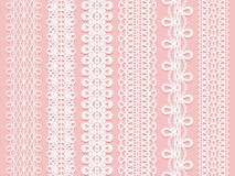 Wide lace ribbons set on a pink background. Stock Photo