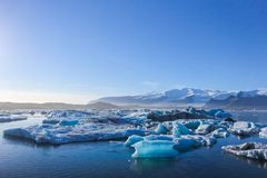 Wide landscape of icebergs floating on the water under the very clear blue sky with copy space. Wide landscape of icebergs floating on the water under the very Royalty Free Stock Photos
