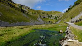 Limestone Scar at Gordale. Wide limestone scar with blue river in foreground Stock Image