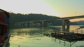 Bridge Over Lake Temenggor And Jetty Houses, KL. Wide low-angle evening still shot of a long concrete  bridge crossing Temenggor Lake, and painted tin-roof jetty stock video footage