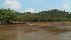 Stilt Path At Bukit Merah Lake,  Malaysia. Wide low-angle panning shot of receded water level, stilt walking path with coloured  flag posts, and tropical stock video footage
