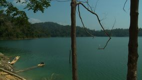 View Of Lake   Orang Asli Village, Temenggor, KL. Wide low-angle still shot view of calm Temenggor Lake, and tropical rain forest Island landscapes from a remote stock footage