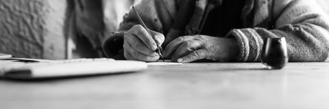 Wide low angle view of an elderly man doing calligraphy writing. Using a nib pen and ink on a sheet of white paper in a monochrome image royalty free stock photo