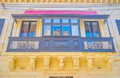 The wide Maltese balcony in Naxxar, Malta. The wide Maltese balcony painted in grey with beautiful carved sculptures below it, Naxxar, Malta royalty free stock photo