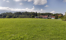 Wide meadow near the Alpine village in Austria stock photography