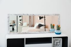 Wide mirror on table near wall. Wide mirror on table near light wall stock photos