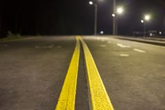 Wide modern smooth empty illuminated with street lamps asphalt highway with bright white marking sign line at night. Speed, safety. Comfortable journey and royalty free stock images