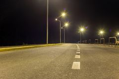 Wide modern smooth empty illuminated with street lamps asphalt highway with bright white marking sign line at night. Speed, safety. Comfortable journey and royalty free stock photography