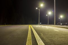 Wide modern smooth empty illuminated with street lamps asphalt highway with bright white marking sign line at night. Speed, safety. Comfortable journey and stock image